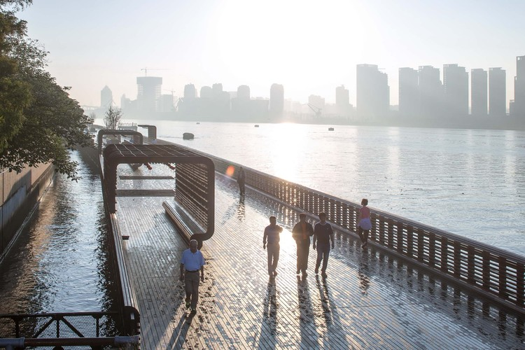 Demonstration Section of Yangpu Riverside Public Space / Original Design Studio, Residents exercising on the footbridge at daybreak. Image © Yong Zhang