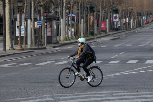 PARIS, FRANCE March 22th 2020 : The Cyclist with medical mask on Champs Elysées empty during the period of containment measures due to the Covid-19 Coronavirus. Image via Shutterstock/ By Frederic Legrand - COMEO