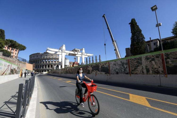 Itália oferece 500 euros para pessoas comprarem bicicletas durante pandemia do coronavírus, Ciclista de máscara pedala perto do Coliseu em Roma. © Alessia Pierdomenico/ Bloomberg, via Mobilize