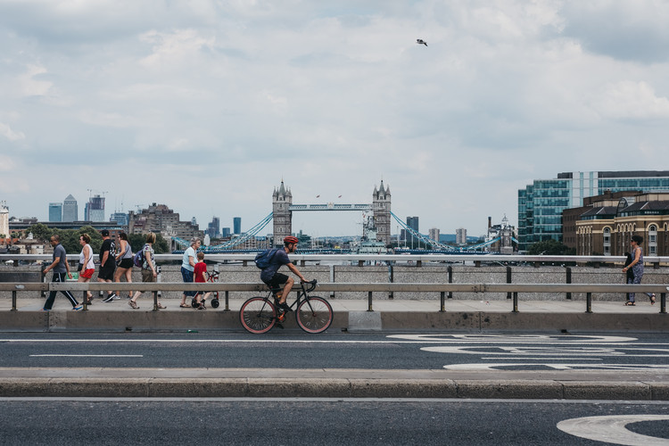 London Introduces Car-Free Streets as Lockdown Eases, Cyclist and pedestrians on London Bridge, London, UK, River Thames and Tower Bridge on the background. Image via Shutterstock/ By Alena Veasey