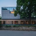 After the renovation, the old stone wall of the first floor of the Chinese restaurant is kept, in contrast to the new materials of the second and third floors. Image © Yilong Zhao