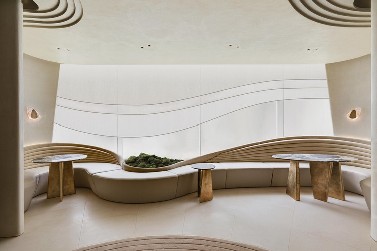 The Garden Pavilion / NCDA, A series of undulating curves are recurring motifs and provide an abstract echo of nature. Lines are cut into the plaster of the ceiling in patterns that suggest raked gravel patterns of a sand garden, while organically shaped sconces and tables are designed to mimic rocks in a garden. Image © Harold De Puymorin