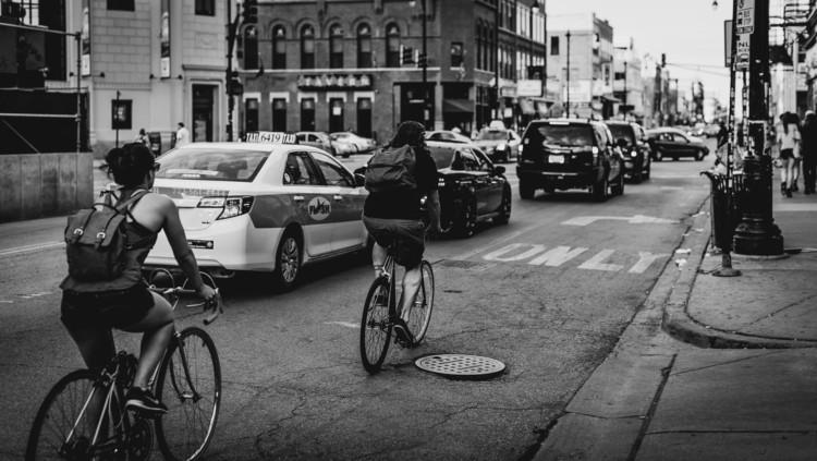 Deslocamentos de bicicleta em uma megacidade: os desafios da extensão territorial, segurança viária e transposição de barreiras, Ciclistas em rua de metrópole. Foto de Adrian Williams, via Unsplash