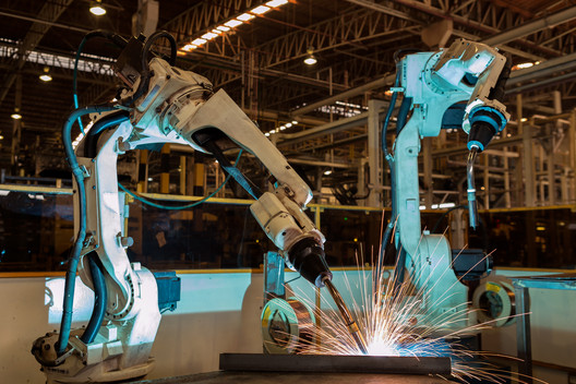 Industrial robots welding automotive part in a car factory. Image © Factory Easy | Shutterstock