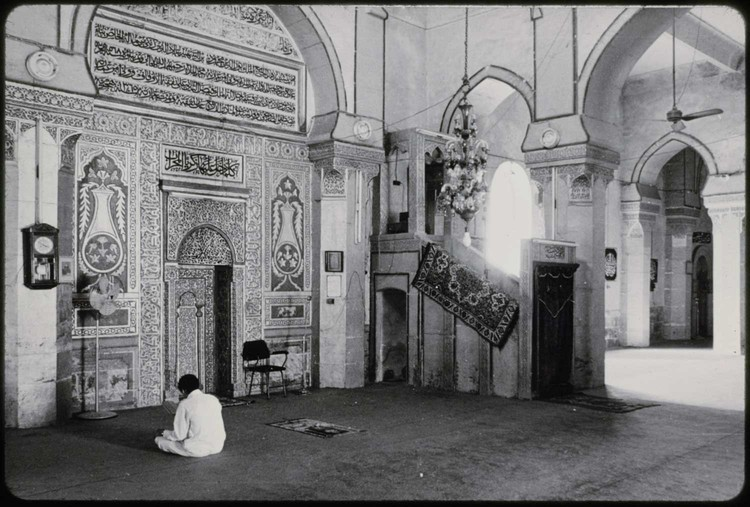 Man seated before the Mihrab in the prayer hall, after reconstruction in 1944. Image © General Authority of Antiquities