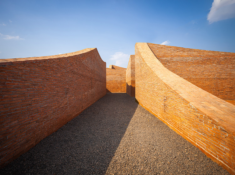 Curved walls at varying heights sprout from the vast landscape. Some slope down to the ground, acting like a door that opens to visitors of an elephant's size. Image © Spaceshift Studio