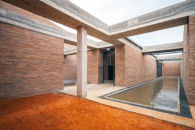 Courtyards of different shapes and sizes open up from the four exhibition galleries. Some are filled with small pools, some with reddish earth just like the landscape outside. Image © Spaceshift Studio