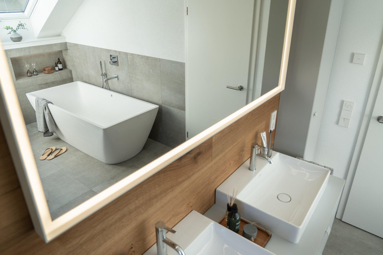 Natural Wood, Gray and White: How to Update a 90's Bathroom, The mirror with dimmable LED lighting visually enlarges the room, which, thanks to partitions has more structure. The floor-level shower offers easy access and comfort with underfloor heating, square overhead shower and hand shower. Image Via Architonic
