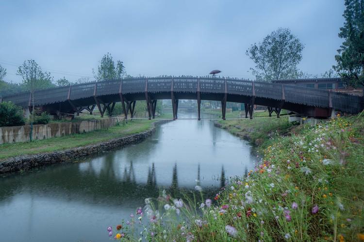the country pedestrian bridge in the misty rain. Image © Timeraw Studio