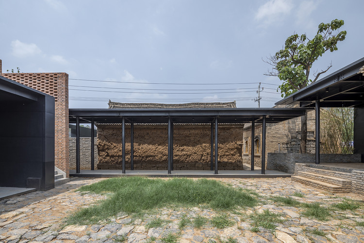 rammed earth, red bricks and steel plates form a dialogue between materials and the times. Image © Weiqi Jin