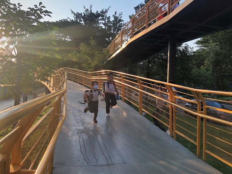 Children hang around the ramp.  Image © Liguo Su