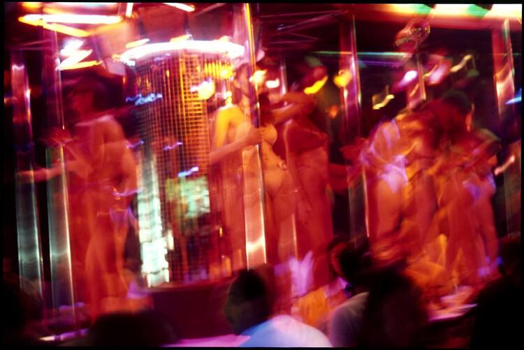 Проститутки танцуют для потенциальных клиентов в баре в районе красных фонарей, Пат Понг, Бангкок, Таиланд.  Изображение через axlright под лицензией CC BY-NC 2.0