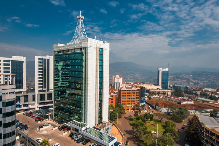 """How """"Smarter"""" Cities Can Exacerbate Inequity, Kigali, Rwanda - September 21, 2018: a wide view looking down on the city centre with Pension Plaza in the foreground and Kigali City Tower in the background against a backdrop of distant blue hills. Image via Shutterstock/ By Jennifer Sophie"""